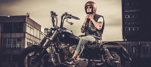 Biker tatuato e la sua motocicletta in stile bobber su strade cittadine