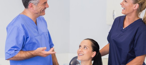 Smiling dentist and nurse speaking with their patient in dental clinic